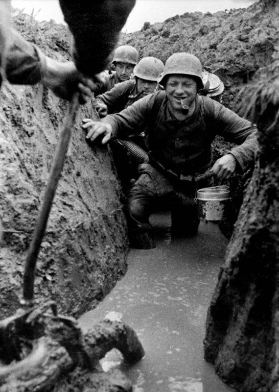 Немецкие солдаты в залитых водой окопах разносят пищу