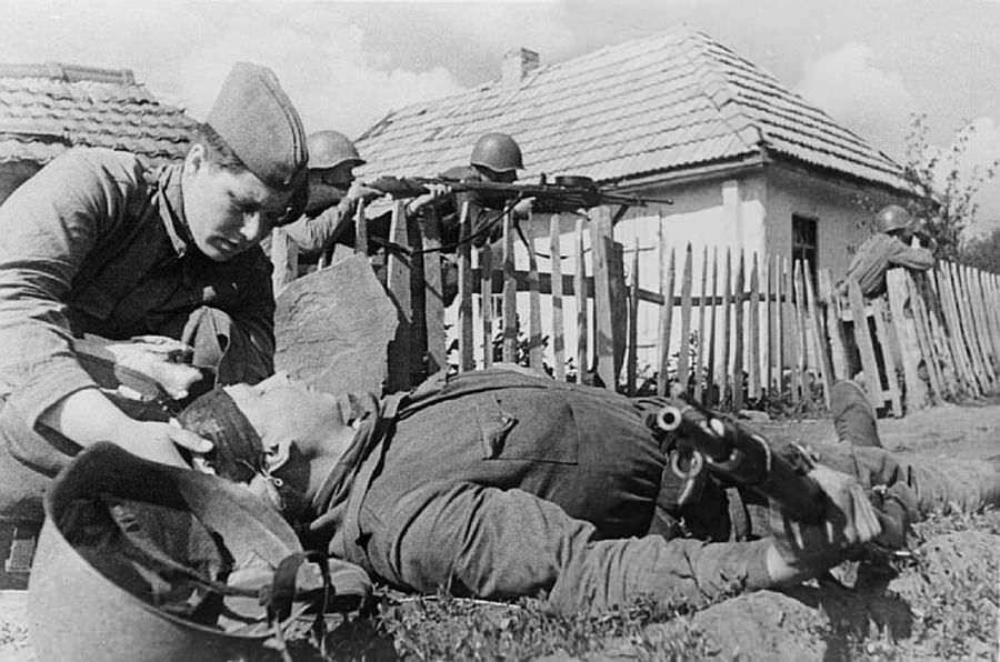 Санитарка перевязывает раненого солдата