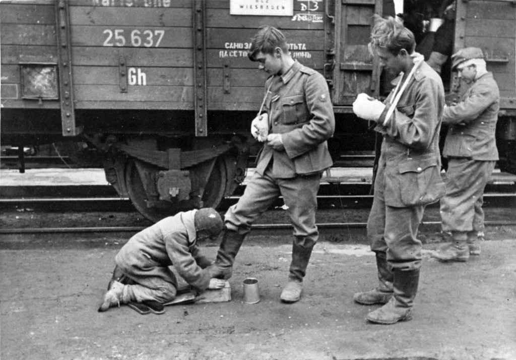 Подросток чистит сапоги немецкому солдату