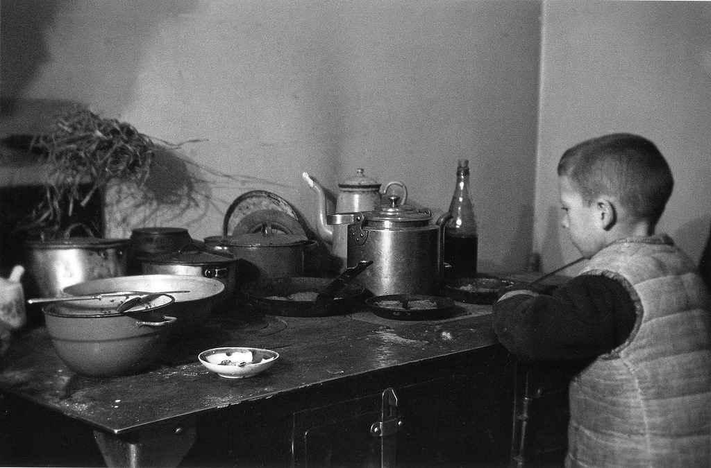 Школьник Миша Никитин у кухонной плиты в блокадном Ленинграде