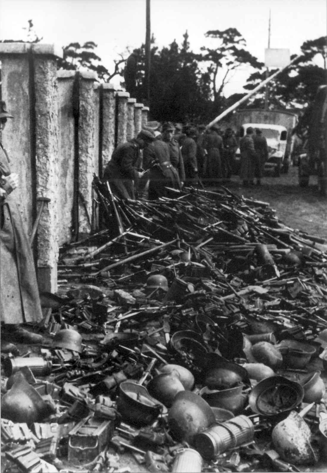 Эвакуируемые немецкие солдаты бросают оружие и снаряжение на улице порта Пиллау