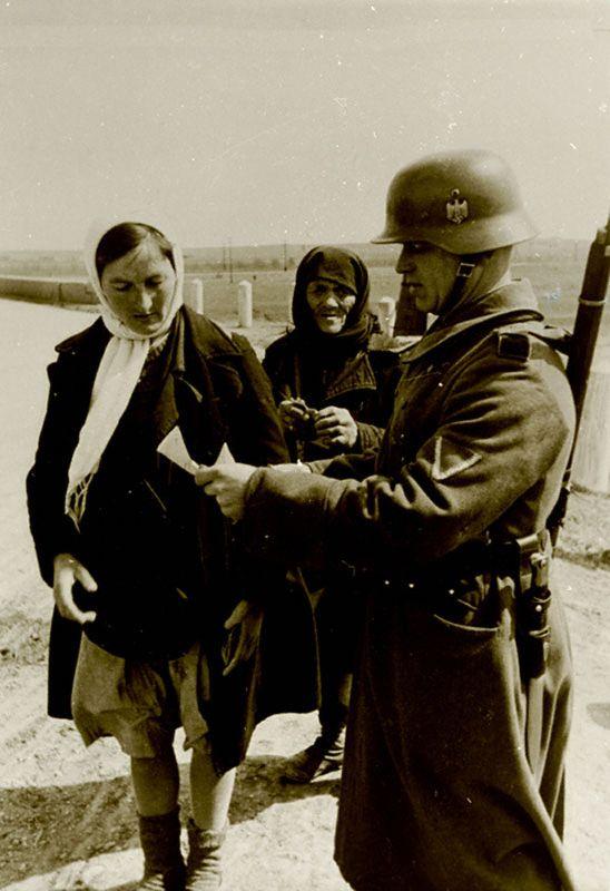 Беженки проходят контрольный пост немцев