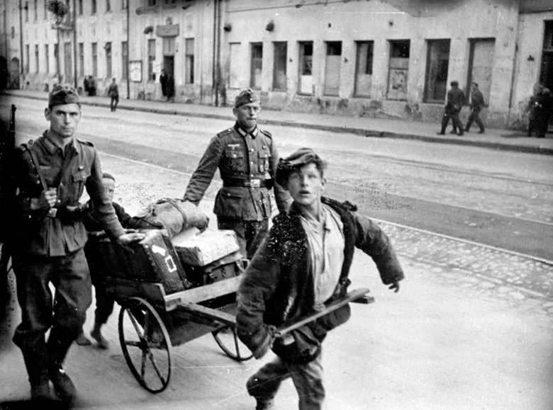 Русские дети на самодельных тачках везут багаж немецких солдат-отпускников на вокзал