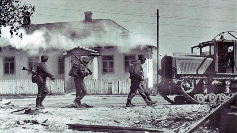 Солдаты войск СС идут по захваченной украинской деревне