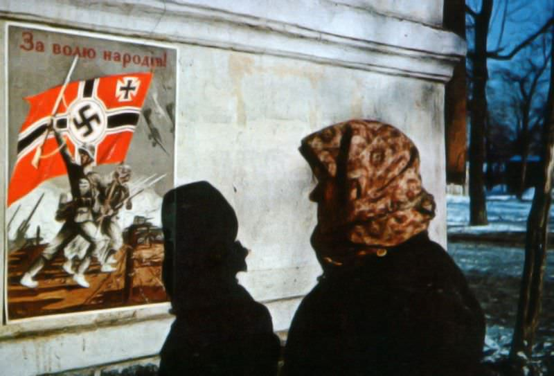 Жительница Харькова рассматривает немецкий плакат