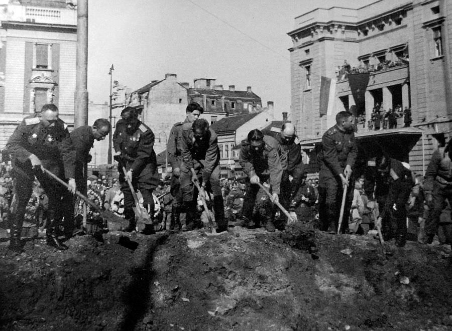 Советские офицеры засыпают братскую могилу советских солдат
