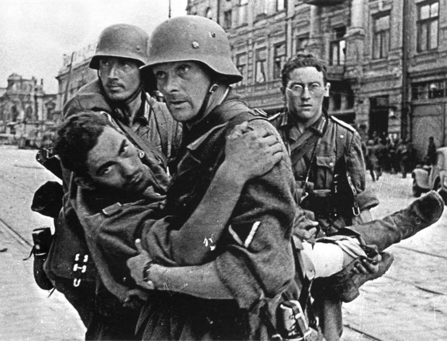 Немецкие солдаты переносят раненного товарища