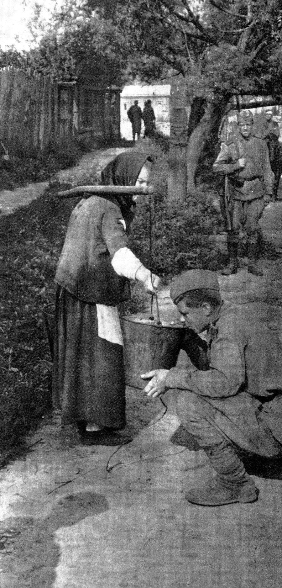 Советский солдат пьет воду из ведра