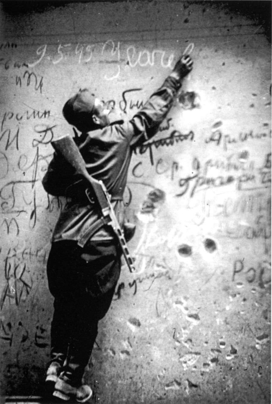 Красноармеец расписывается на стене рейхстага