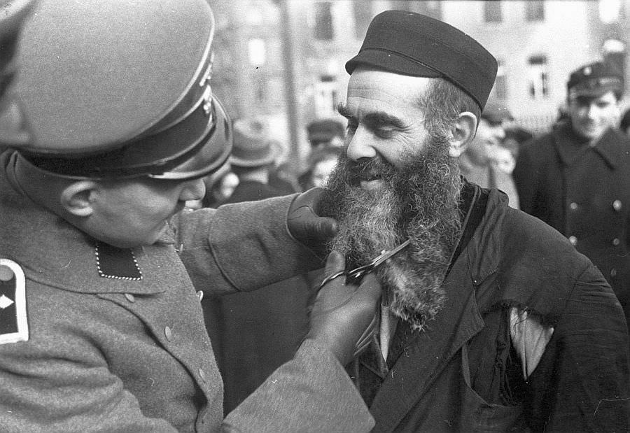 Немецкий полицейский остригает бороду еврею