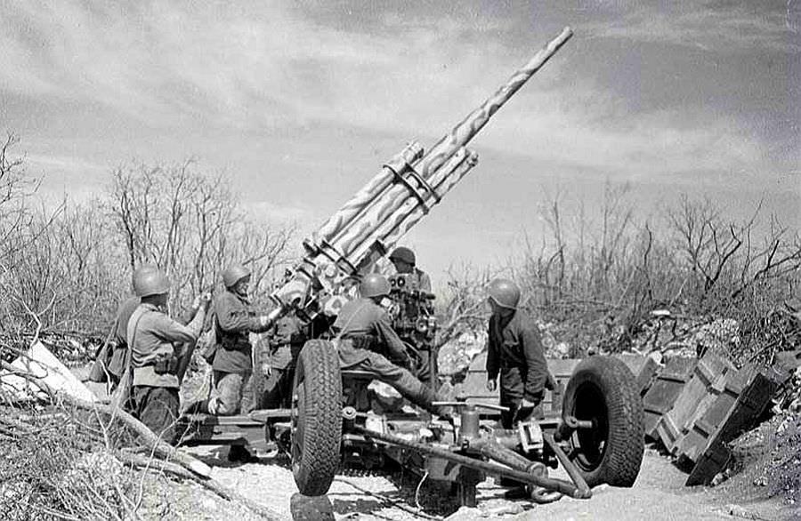 Расчет орудия зенитной батареи ведет огонь по противнику