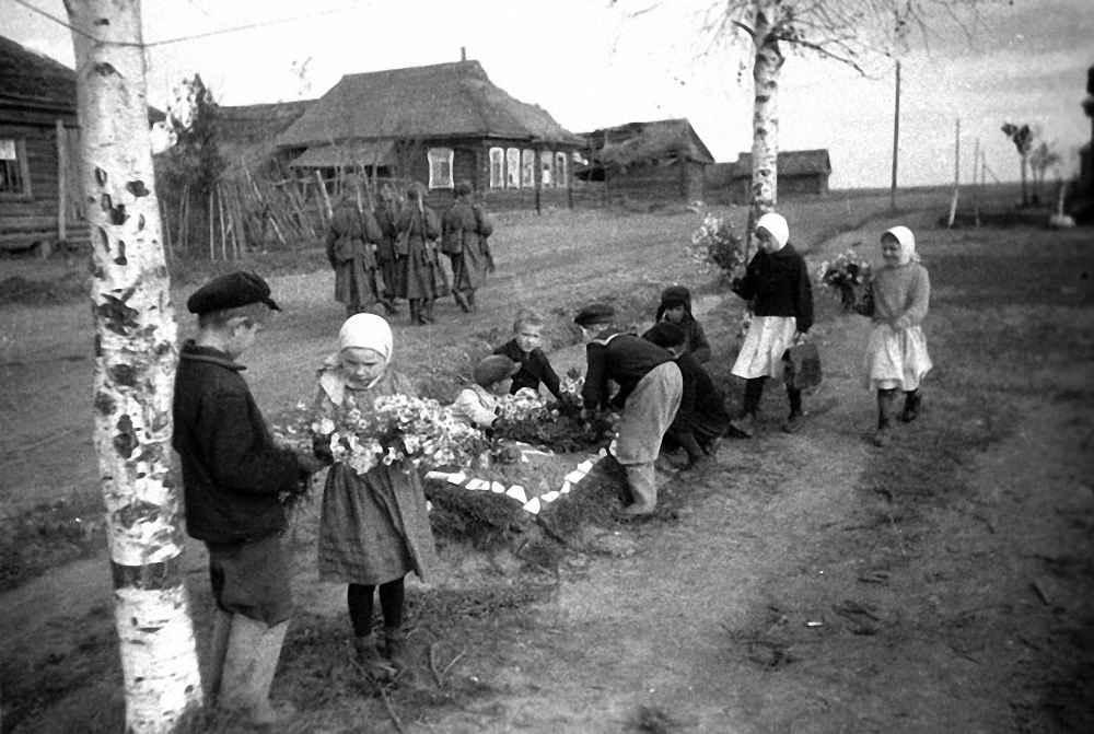 Дети возлагают цветы на могилы советских солдат