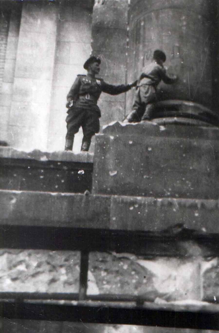 Сын полка ставит автограф на колонне Рейхстага