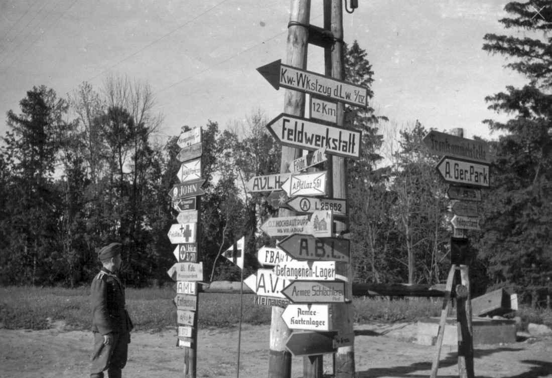 Унтер-офицер вермахта у дорожных указателей в районе оккупированного Курска